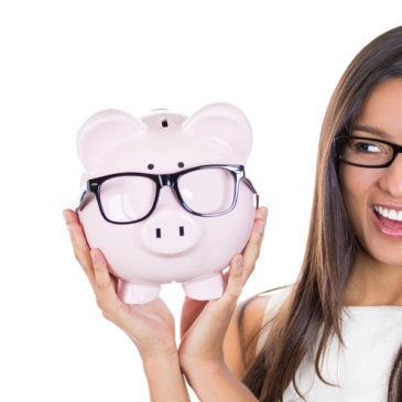 Young woman holding a piggy bank wearing glasses.